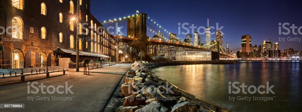 Brooklyn Bridge Park waterfront in evening with view of skyscrapers of Lower Manhattan and the Brooklyn Bridge. New York City stock photo
