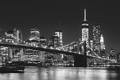 Night at Brooklyn bridge with illuminating buildings from Manhattan in background. New York City, US. Black and White image.