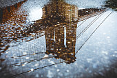 The Brooklyn Bridge is reflected in a puddle. Brooklyn, NY. USA