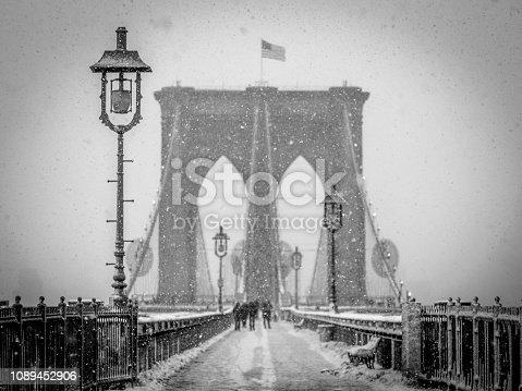 A snowy scene of people in silhouette walking across the Brooklyn Bridge from Manhattan to Brooklyn.