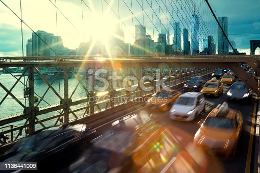 New York City, Brooklyn Bridge with heavy car traffic, skyscrapers in Lower Manhattan in the background, image against sunset light with lens flares.