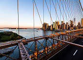 NYC / USA - 26th June 2019: Brooklyn Bridge with view of the Hudson river and skyscrapers at sunrise, NYC