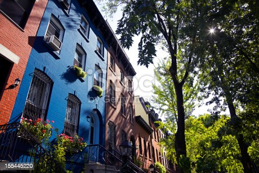 A row of brownstones in Brooklyn, New York. One blue row home and the rest are red.