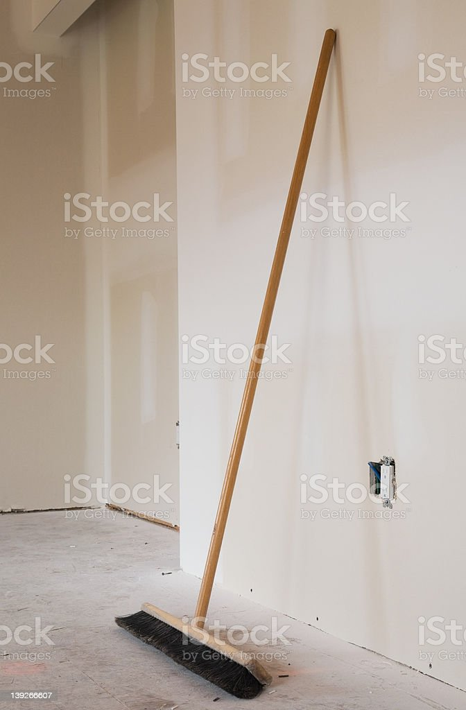 Broom leaning against a wall stock photo