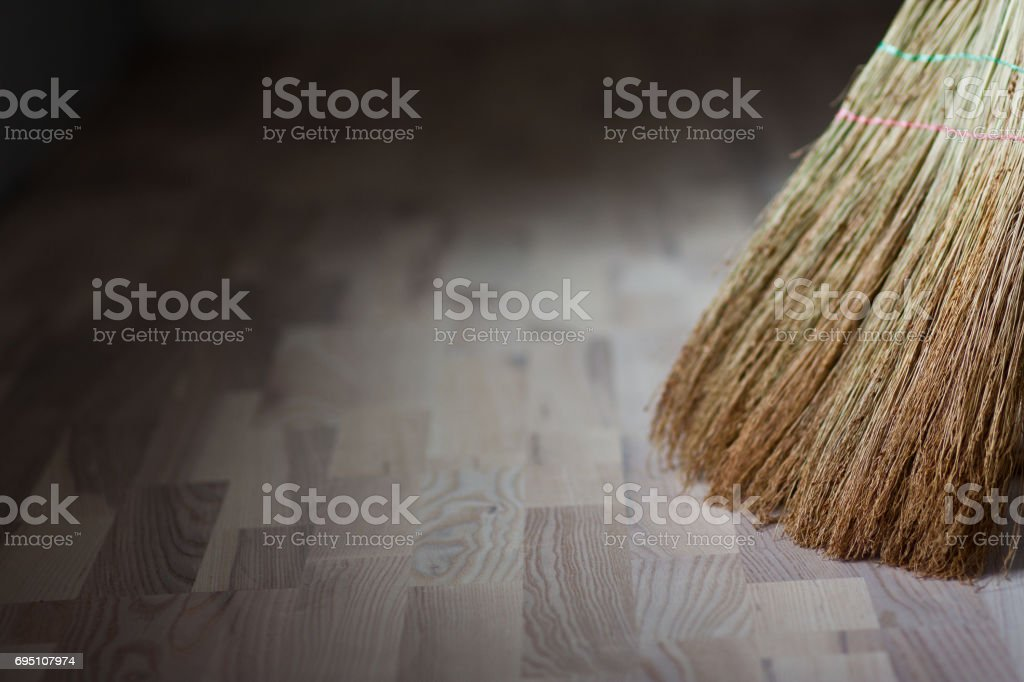 A broom stands on a wooden floor stock photo