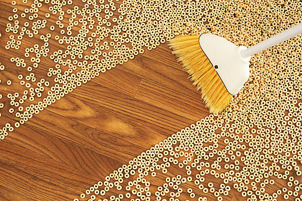 broom sweeping a path through cereal - sweeping stock pictures, royalty-free photos & images