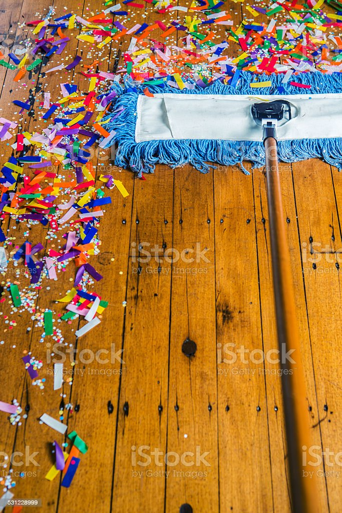 Broom sweeping up confetti stock photo