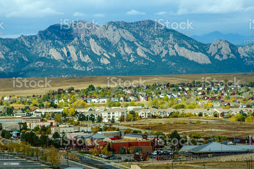 """Broomfield, Colorado and the Flatiron Mountain Range Broomfield, Colorado, USA - October 19, 2015: Urban sprawl from the developments in Broomfield, Colorado apprach the majestic range of the Flatiron Mountains. Carpenters work on a new sledding attraction at the top of Vail Mountain which overlooks the Colorado Rockies and Vail Pass. The Flatirons are rock formations in the western United States, near Boulder, Colorado, consisting of flatirons. There are five large, numbered Flatirons ranging from north to south along the east slope of Green Mountain, and the term """"The Flatirons"""" sometimes refers to these five alone. Numerous additional named Flatirons are on the southern part of Green Mountain, Bear Peak, and among the surrounding foothills. Taken at sunrise from a height of over 100 feet in Broomfield, Colorado. Apartment Stock Photo"""