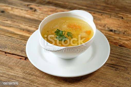 Broth - chicken soup with noodles in a white bowl on wood background in rustic stye