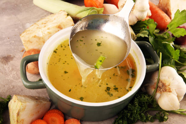 broth with carrots, onions various fresh vegetables in a pot - colorful fresh clear spring soup. rural kitchen scenery vegetarian bouillon stock - caldo imagens e fotografias de stock