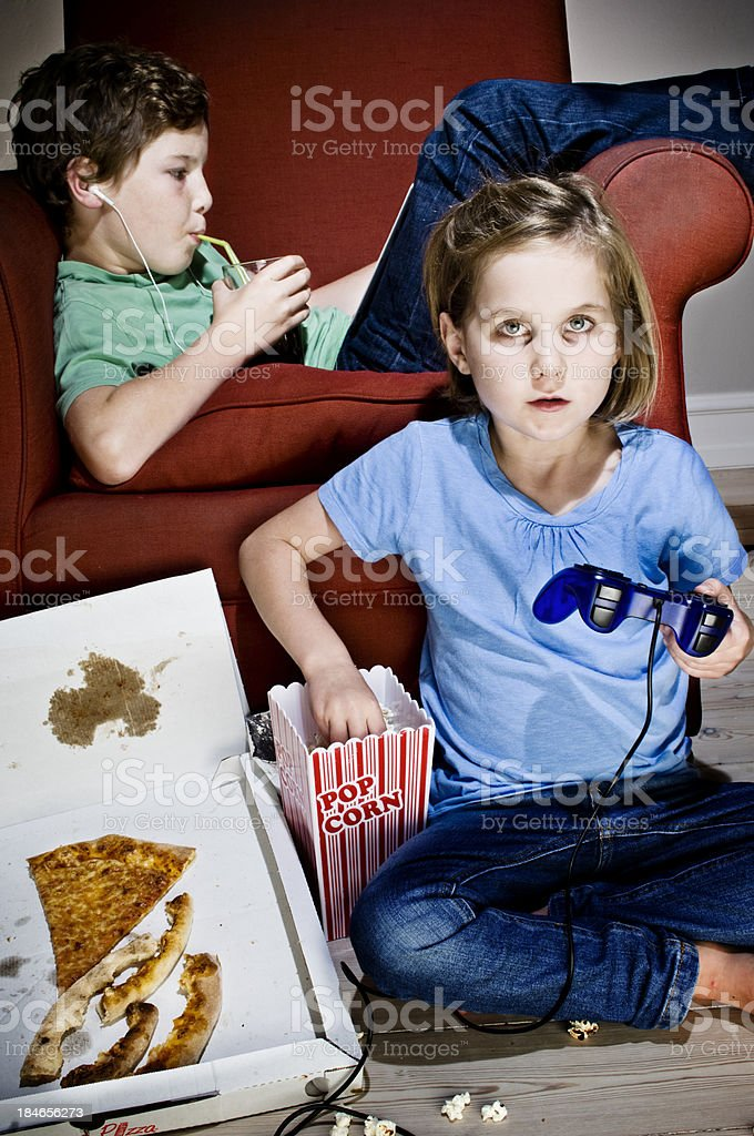 Brother and Sister Addicted to TV and Junk Food royalty-free stock photo