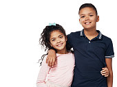 Studio portrait of a happy boy and girl embracing one another against a white background