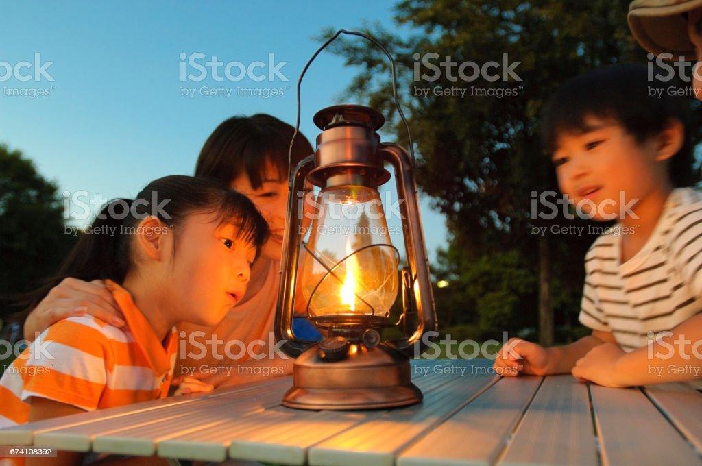 弟と妹と母はランタンの明かりを見つめて ストックフォト