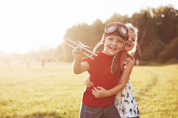 Bruder und Schwester spielen zusammen. Zwei Kinder spielen mit einem hölzernen Flugzeug im Freien – Foto