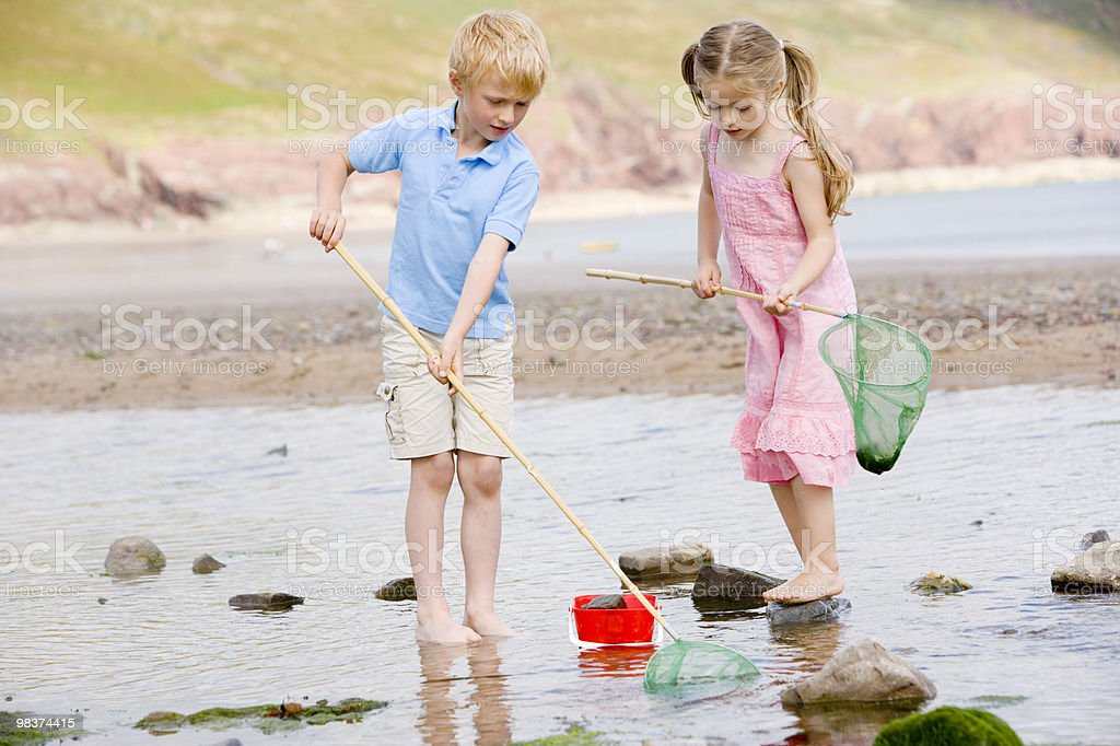 Brother and sister at beach with nets royalty-free stock photo