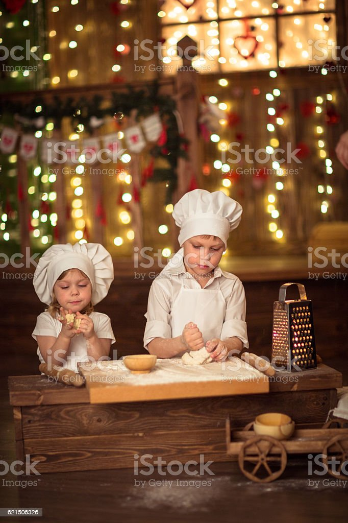 brother and sister baked, the dough is rolled out foto stock royalty-free