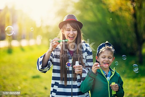 618034312 istock photo Brother and sister blowing bubbles on Spring day 1091665588