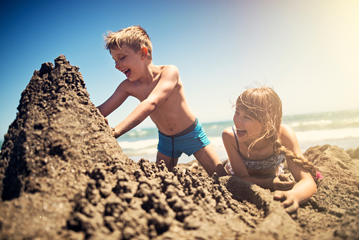 Happy kids are building sandcastle on a beach on a sunny summer day. Andalusia, Spain.