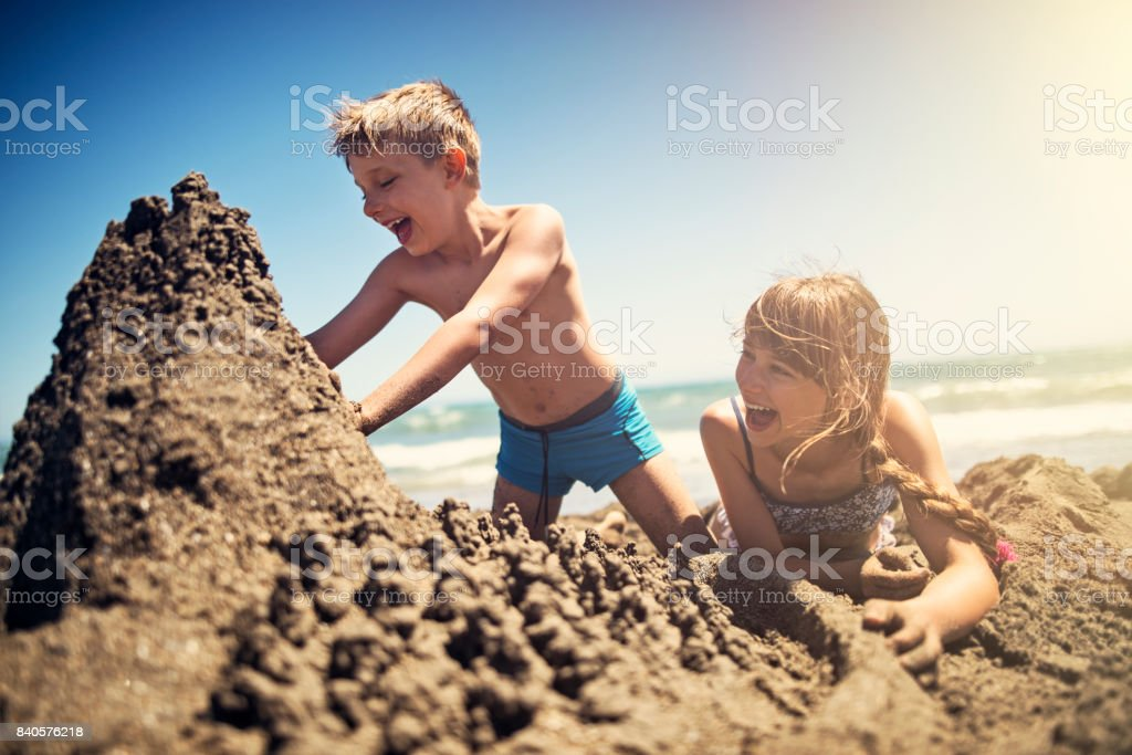 Brother and sister building a sandcastle on beach stock photo