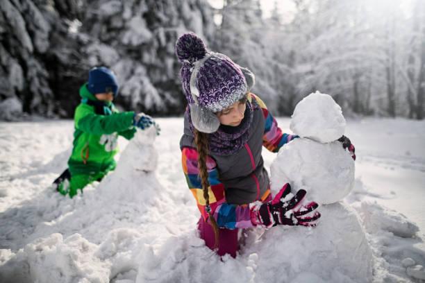 bruder und schwester beim schneemannbauen im winterwald - schneemann bauen stock-fotos und bilder