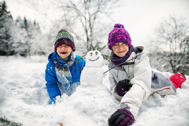 bruder und schwester beim schneemannbauen an einem wintertag - schneemann bauen stock-fotos und bilder