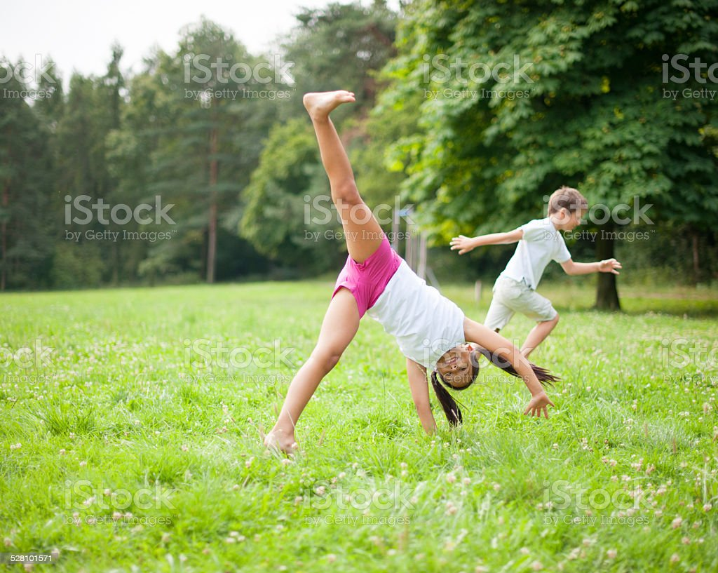 Brother and sister cartwheeling in meadow stock photo