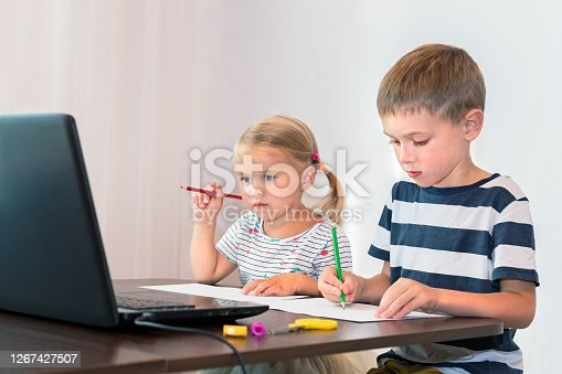 Brother and sister draw at home in front of their laptop. The concept of online learning.