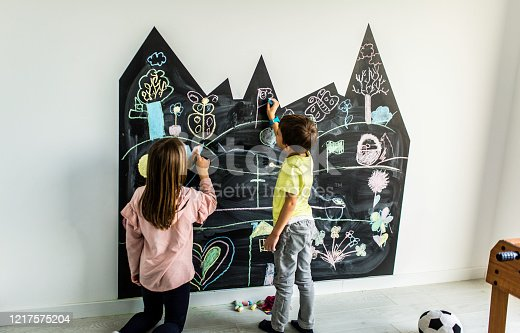 Brother and sister drawing on the blackboard in their room Stock photo