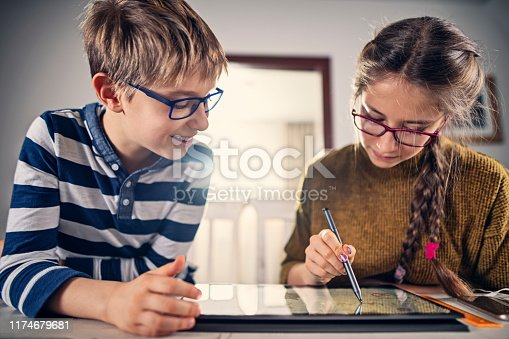 Brother and sister enjoying drawing on modern touch screen laptop using digital pen Nikon D850