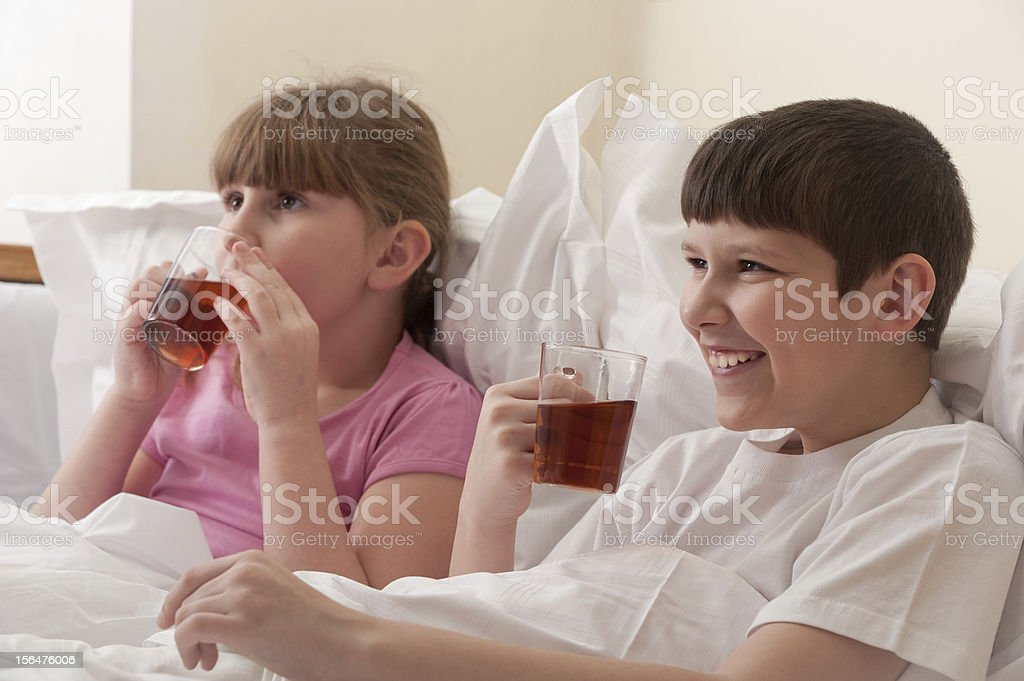 Brother and sister drinking tea in bed. Indoors. Close-up. royalty-free stock photo