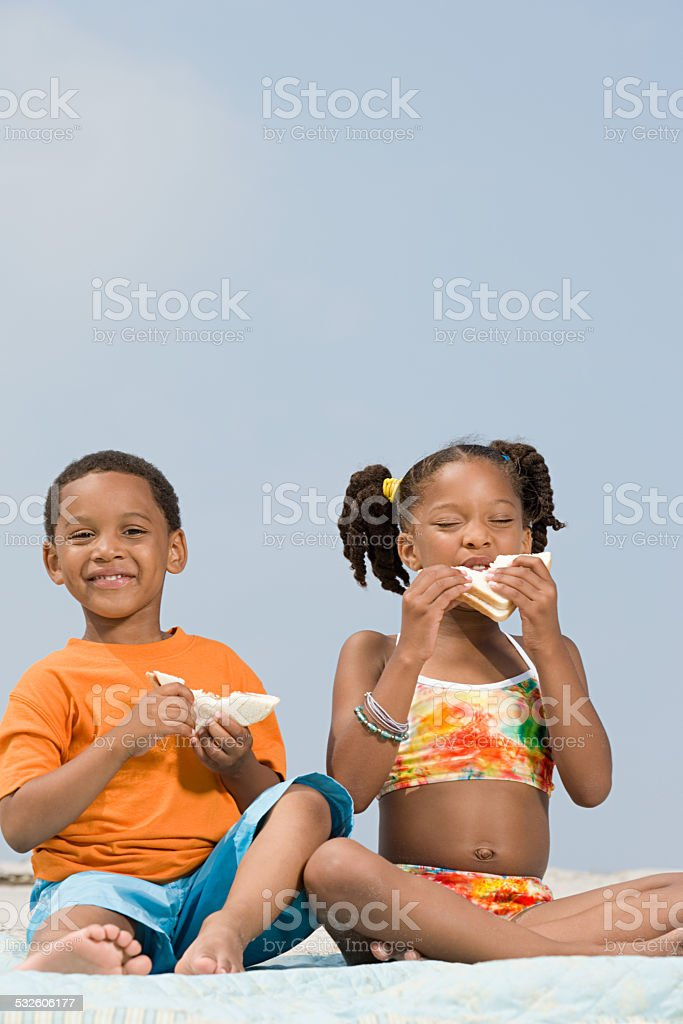 Brother and sister eating sandwiches stock photo
