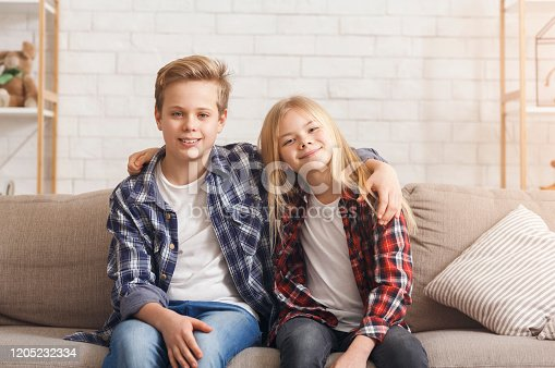 Cute Brother And Sister Embracing Smiling To Camera Sitting On Couch At Home. Siblings Friendship Concept