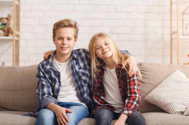 Brother And Sister Embracing Smiling Sitting On Couch At Home Cute Brother And Sister Embracing Smiling To Camera Sitting On Couch At Home. Siblings Friendship Concept brother stock pictures, royalty-free photos & images