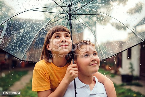 Brother and sister standing underneath clear umbrella and looking the rain falling