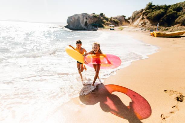 Bruder und Schwester genießen Sommermorgen am Strand – Foto