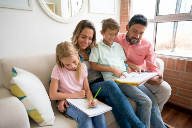Brother and sister enjoying their time colouring on their notebooks and loving parents having fun with them stock photo