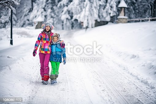 Brother and sister enjoying playing on winter day. The kids are walking on snowy road and embracing. Nikon D850