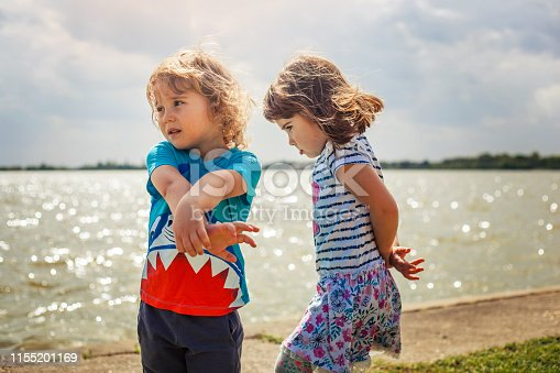 Brother and sister feeling sad by the lake