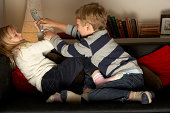 Brother And Sister Fighting Over Remote Control In Living Room At Home
