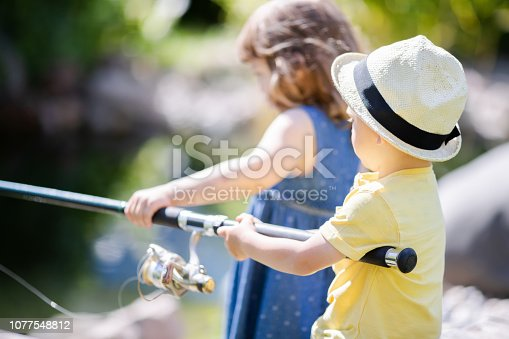 Brother and sister fishing together. Kids friends holding fishing rod. Warm summer day