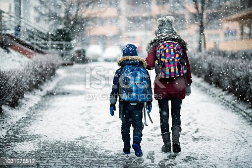Brother and sister going to school on winter day. Elder sister aged 12 is walking her younger brother aged 8 to school. Nikon D850