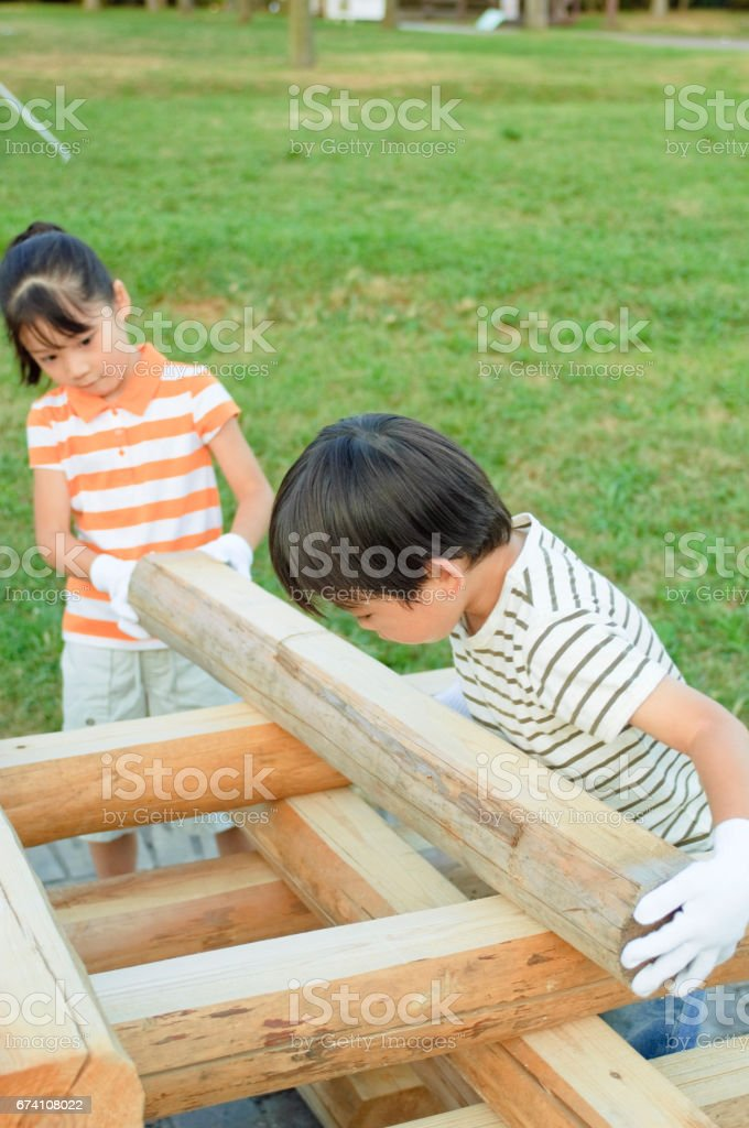 Brother and sister having a campfire wood royalty-free stock photo