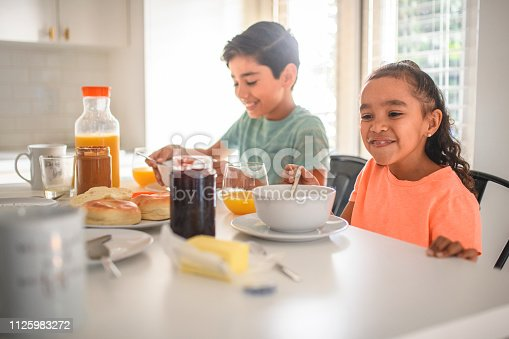 Portrait of smiling boy and his sister having breakfast. Male child is sitting near sister at kitchen island. They are wearing casuals at home.