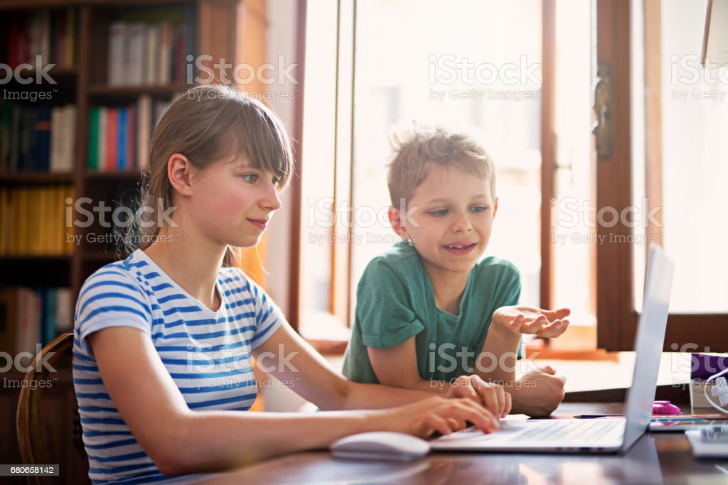 Brother and sister having fun coding at home stock photo