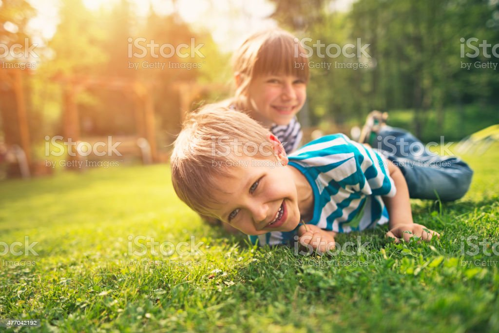 Brother and sister having fun on garden lawn stock photo