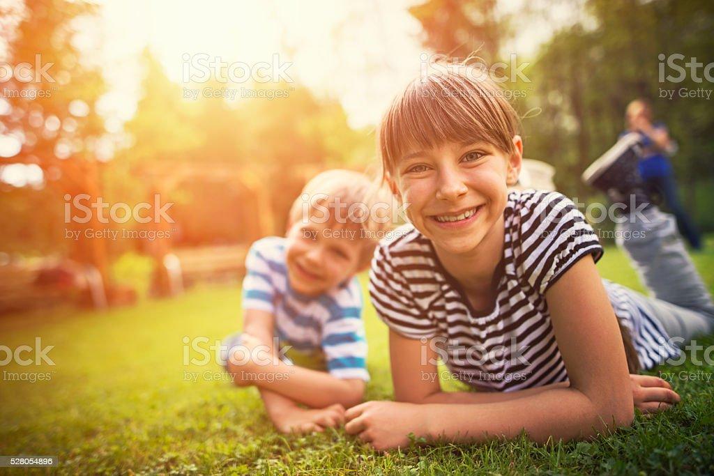 Bruder und Schwester, die Spaß auf Garten Rasen Lizenzfreies stock-foto