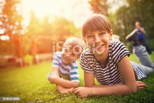 istock Brother and sister having fun on garden lawn 528054896