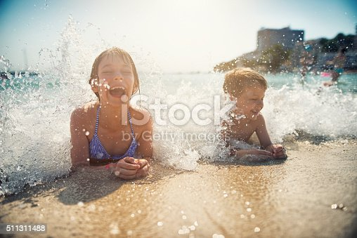 istock Brother and sister having fun splashed in sea 511311488