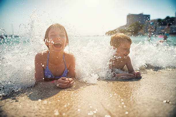 brother and sister having fun splashed in sea - spain solar bildbanksfoton och bilder