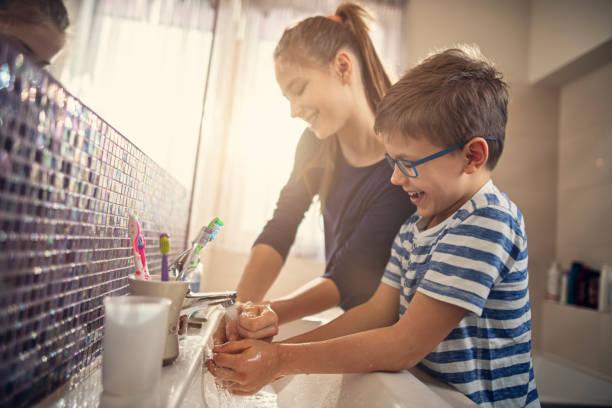 bruder und schwester haben spaß am händewaschen - hände wasser wasserhahn kinder lachen stock-fotos und bilder